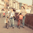 Two Beautiful Women Walking in the City with Bicycles and Bags - Stok fotoraf
