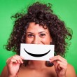 Young Woman with Smiley Emoticon on Green Background — Stockfoto #13773952