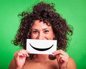 Mujer joven con emoticon sonriente sobre fondo verde — Foto de Stock