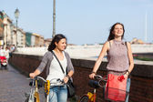Two Beautiful Women Walking in the City with Bicycles and Bags — Stock Photo