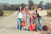 Grupo hippie, caminhando em uma estrada rural — Foto Stock