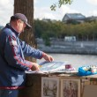 Mature man with his paint works near river — Stock Photo