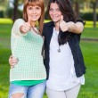 Happy Female Friends at Park with Thumbs Up — Stock Photo #14364605