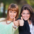 Happy Female Friends at Park with Thumbs Up — Stock Photo #14364659