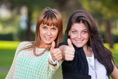 Happy Female Friends at Park with Thumbs Up — Stock Photo