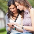 Two Beautiful Women Sending Messages with Mobile — Stock Photo #14489285