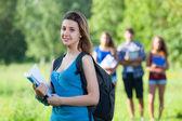 Joven estudiante en el parque con otros amigos — Foto de Stock