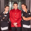 Stock Photo: Bellboy with Two Beautiful Chambermaids
