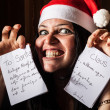 Stock Photo: Bad Woman with Santa Hat destroying a Letter