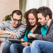 Three Friends with Tablet PC on a Sofa - Stockfoto