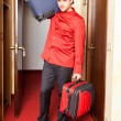 Tired Bellboy with Luggages - Stock Photo