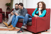 Bored Woman and Men Playing with Tablet PC — Stock Photo