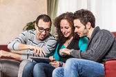 Three Friends with Tablet PC on a Sofa — Стоковое фото