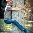 Funny Man Clinging to a Tree - Stock Photo