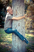 Funny Man Clinging to a Tree — Stock Photo