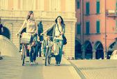 Zwei schöne Frauen, die zu Fuß in die Stadt mit Fahrrädern und Taschen — Stockfoto