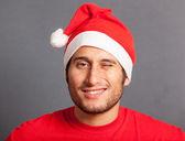 Noel baba şapkası olan genç adam — Stok fotoğraf