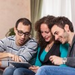 Three Friends with Tablet PC on a Sofa — Stock Photo