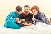 Friends on the Bed with Tablet PC — Stockfoto