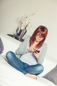 Beautiful Young Woman with Smartphone on the Sofa — Stock Photo