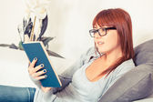 Beautiful Young Woman with a Book on the Sofa — Stock Photo