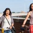 Stock Photo: Two Beautiful Women Walking in the City with Bicycles and Bags