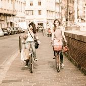 Twee mooie vrouwen lopen in de stad met fietsen en tassen — Stockfoto