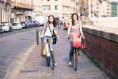 Bisiklet ve çantaları ile şehir içinde yürüyen iki güzel kadın — Stok fotoğraf