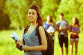 Jovem estudante feminino no parque com outros amigos — Foto Stock