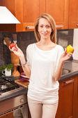 Jovem mulher segurando vegetais na cozinha — Foto Stock