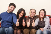 Happy Family on the Sofa with Thumbs Up — Stock Photo