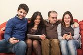 Happy Family on the Sofa with Electonic Devices — Stock Photo
