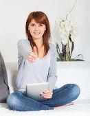 美丽的年轻女子,通过使用 tablet pc 在沙发上 — 图库照片