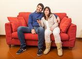 Młoda para, oglądanie tv na kanapie — Zdjęcie stockowe