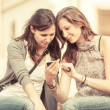 Stock Photo: Two Beautiful Women Sending Messages with Mobile