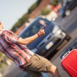 Young Man Hitchhiking along the Road - Stock Photo