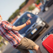 Young Man Hitchhiking along the Road — Stock Photo