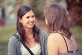 Twee jonge vrouwen op een bankje in het park — Stockfoto