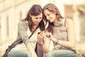 Två vackra kvinnor skickar meddelanden med mobil — Stockfoto