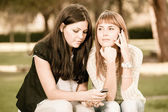 Two Young Women with Mobile Phone — Stockfoto