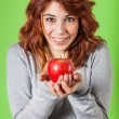 Teenage Girl Holding a Red Apple on Green Background — Stock Photo #19880859