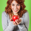 Stock Photo: Teenage Girl Holding a Red Apple on Green Background