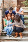 Grupp tonåriga vänner med tabletpc — Stockfoto