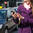 Stock Photo: Young WomTalking on Mobile waiting for Taxi