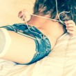 Young Nude Woman on Bed Listening Music - Stock Photo