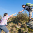 Man Helping His Girlfriend Hiking — Stock Photo