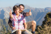 Młoda para z kciuki do góry na szczyt góry — Zdjęcie stockowe