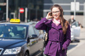 Young Woman Talking on Mobile waiting for Taxi — Stock Photo