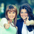 Happy female friends at park with thumbs up — Stock Photo #25989607
