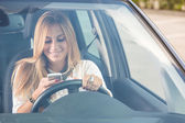 Young woman sending messages while driving — Stock Photo